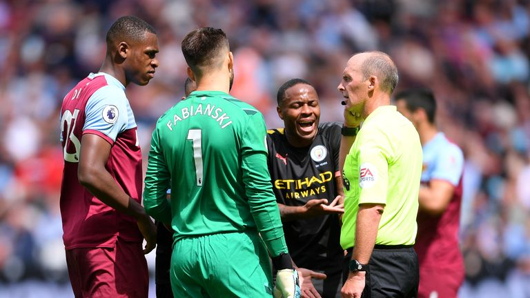 Players from both sides gather around referee Mike Dean after Manchester City's third goal is disallowed by VAR
