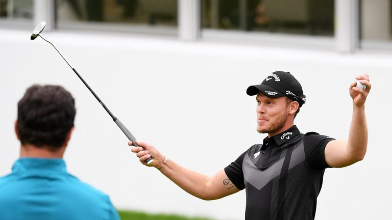 Willett takes the acclaim of the crowd as Jon Rahm watches on