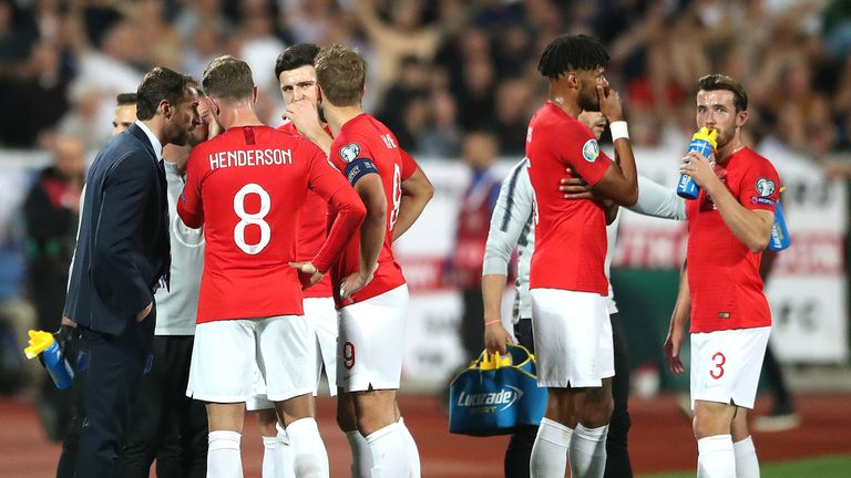 England players talk among themselves during a temporary break in play following racist chanting in Sofia