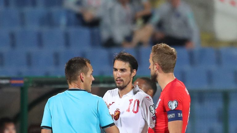 Team captains Popov and Harry Kane speak with referee Ivan Bebek during the qualifier