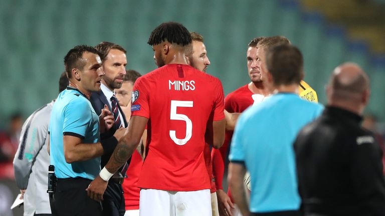 Mings speaks with officials during the clash with Bulgaria