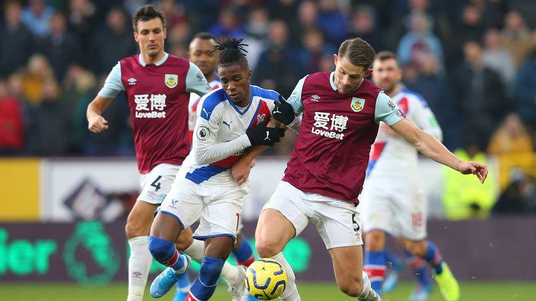 Zaha challenges for the ball with Burnley's James Tarkowski