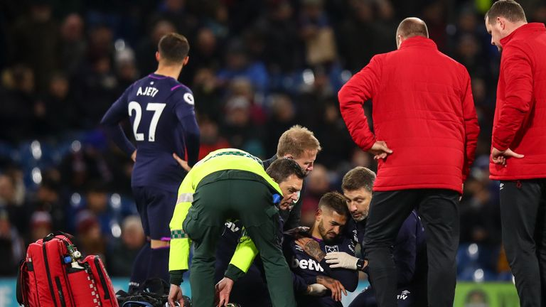 Lanzini holds his shoulder as he receives medical treatment on the pitch at Turf Moor