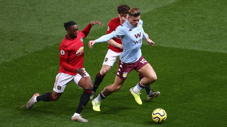 Grealish tries to evade Manchester United duo Aaron Wan-Bissaka and Daniel James