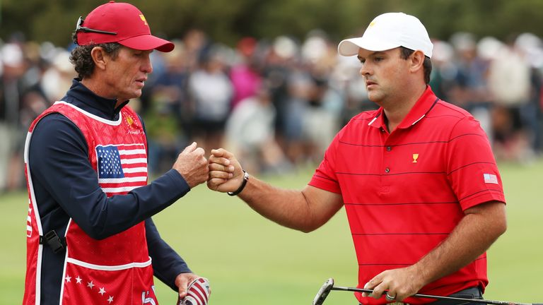 Reed and his caddie and swing coach Kevin Kirk bump fists after the first hole on Sunday