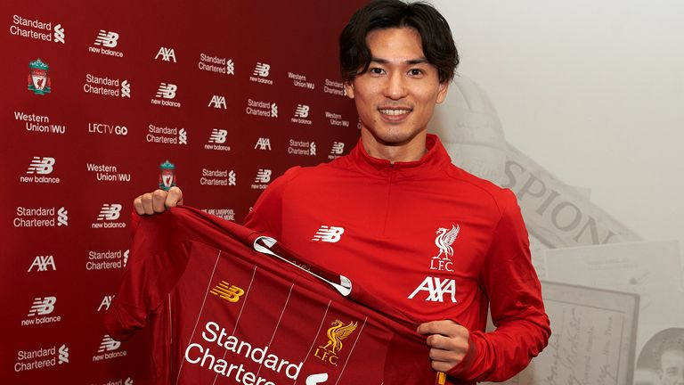 Takumi Minamino pictured with a Liverpool shirt after signing