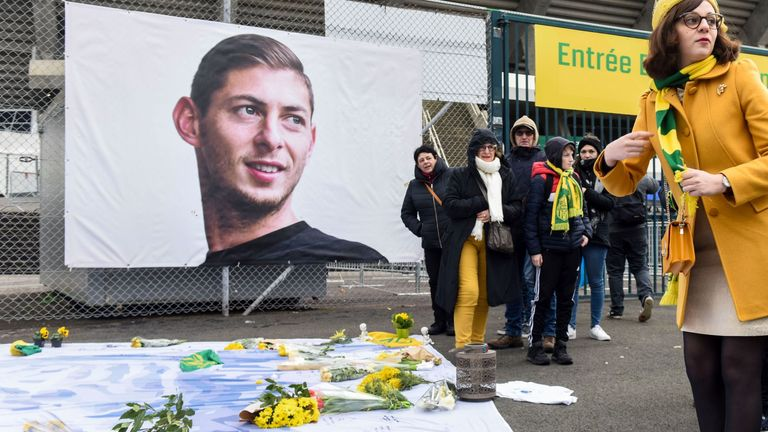 People pay homage and lay flowers in front of a portrait of Nantes' Argentinian forward Emilianio Sala