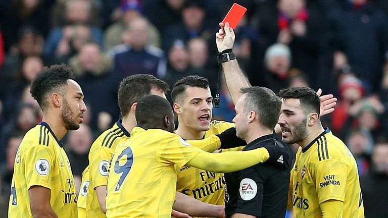 Referee Paul Tierney shows a red card to Pierre-Emerick Aubameyang