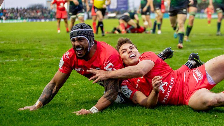 Toulouse's Pita Ahki celebrates scoring a try with Antoine Dupont.