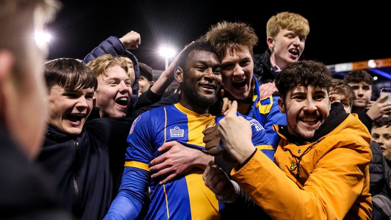 Shrewsbury fans celebrate on the pitch as they set up a tie with Liverpool