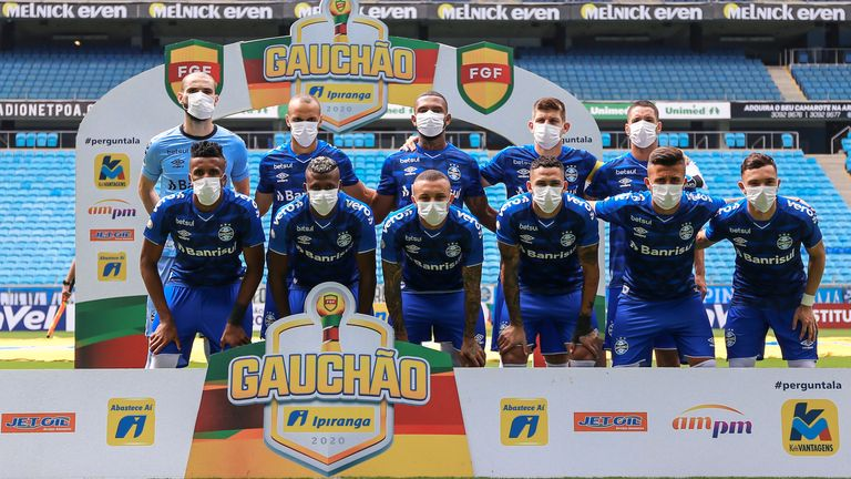 The Gremio players pose for a photo wearing masks before the match against Sao Luiz