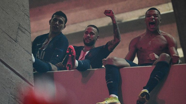 Neymar and Kylian Mbappe celebrate on a balcony with fans outside the ground