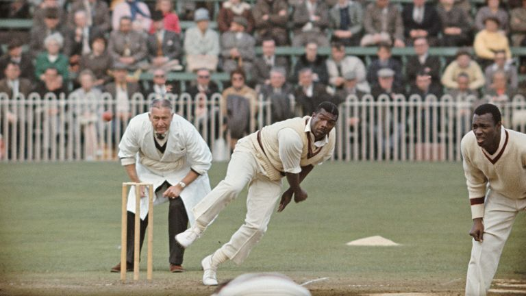 Charlie Griffith in action as umpire Syd Buller and Wes Hall (r) look on during a tour match of England in 1966