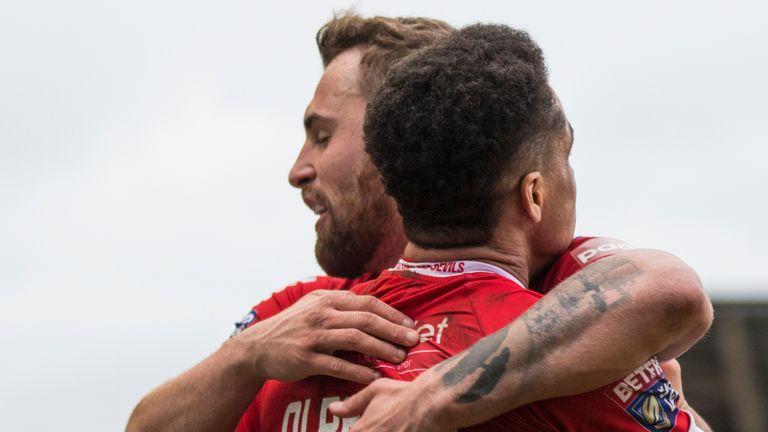 Turgut celebrates with former Salford team-mate Derrell Olpherts
