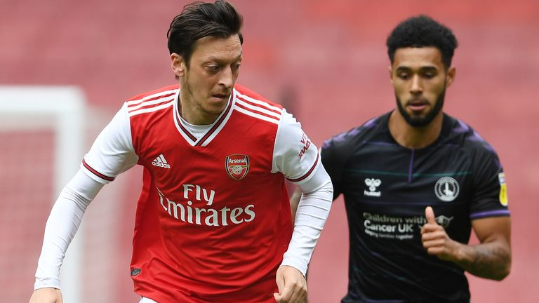 Arsenal's Mesut Ozil breaks past Charlton's Andre Green during a friendly match at the Emirates