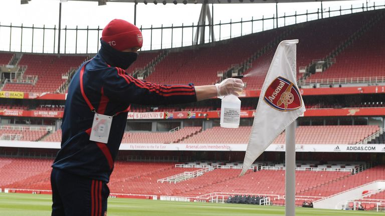 A groundstaff member cleans the corner flag before Saturday's friendly match between Arsenal and Charlton at the Emirates