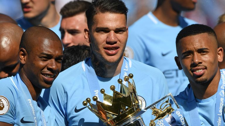 Ederson poses with the Premier League trophy last season