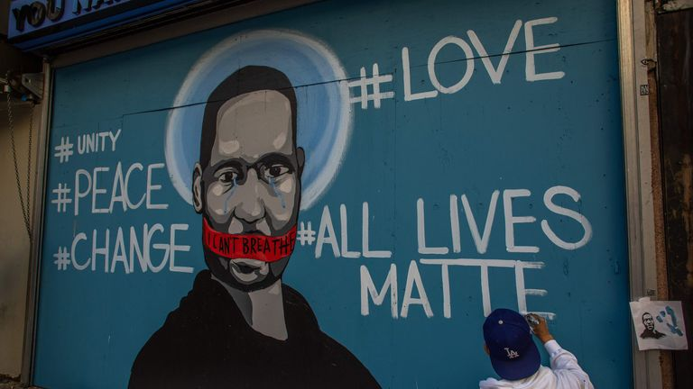 The artist Celos paints a mural in Downtown Los Angeles in protest against the death of George Floyd