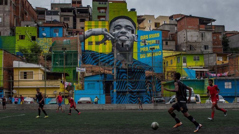 Children playing in Jardim Peri in front of a mural of local hero Jesus