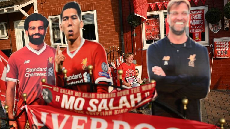Liverpool fan Emily Farley waits for the result of Chelsea vs Man City outside her home in Liverpool, decorated with banners and cut-outs