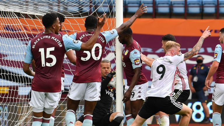 Sheffield United players appeal for a goal as Aston Villa goalkeeper Orjan Nyland appears to hold the ball over the line