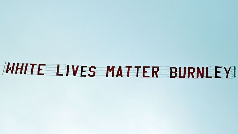 A banner reading 'White Lives Matter Burnley' is towed by a plane above the stadium during the Premier League match between Manchester City and Burnley at the Etihad Stadium
