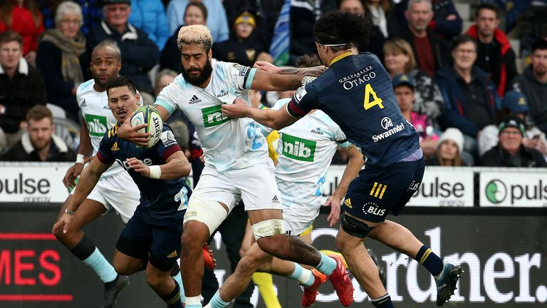 Akira Ioane of the Blues is tackled by Highlanders' Pari Pari Parkinson