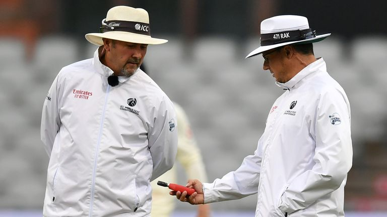 Umpires Richard Illingworth (L) and Richard Kettleborough examine the light meter reading during the second Test between England and Pakistan