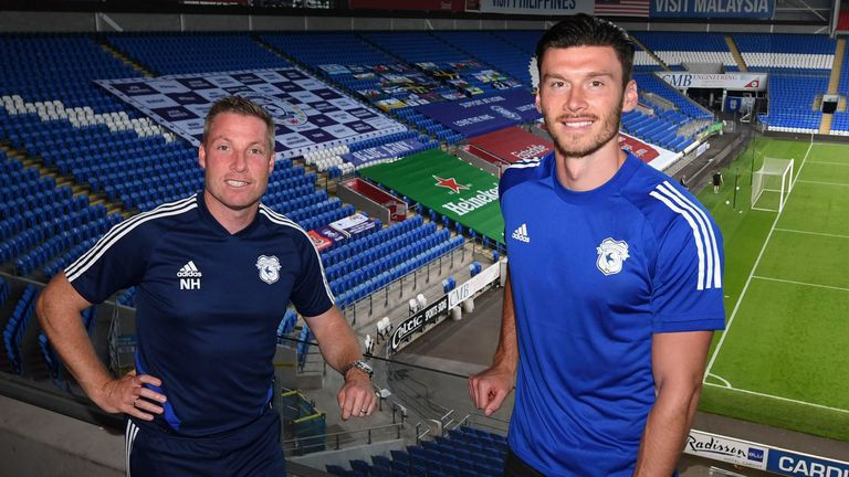 Moore pictured with Cardiff boss Neil Harris after completing his move