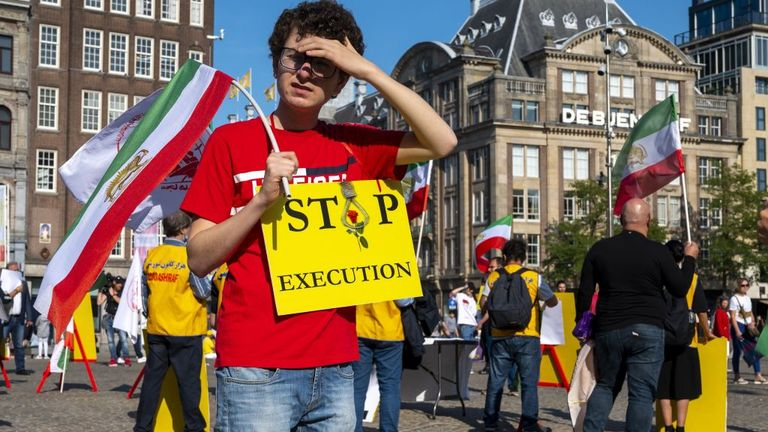 A man holds a sign and a Iranian flag during a demonstration on the Dam Square in Amsterdam