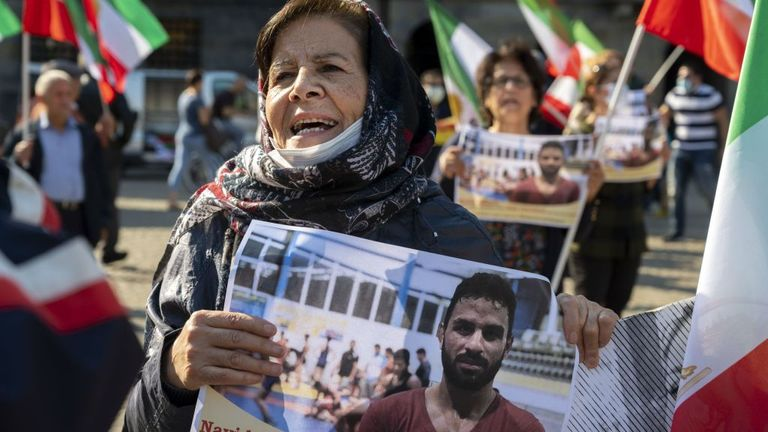 A woman holds a portrait of Iranian wrestler Navid Afkari during a demonstration on the Dam Square in Amsterdam, the Netherlands