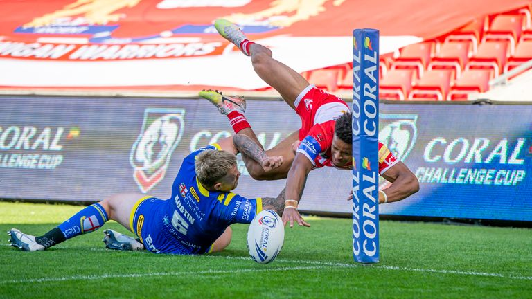 Blake Austin pushes St Helens's Regan Grace into touch before he can touch down for a try