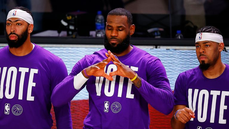 Anthony Davis, LeBron James and Quinn Cook of the Los Angeles Lakers kneel during the National Anthem