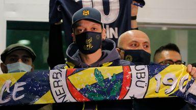 Mesut Ozil held aloft a Fenerbahce scarf on arrival in Turkey on Monday