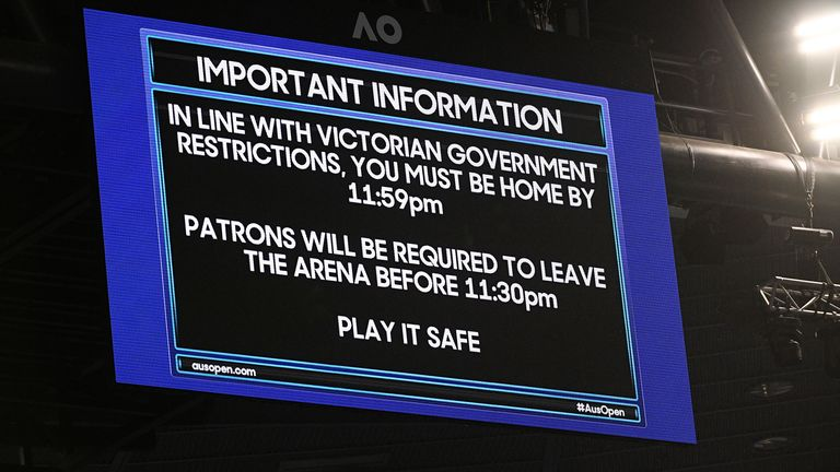 An electronic board on Rod Laver Arena reminds patrons about the lockdown start time during the third round match between Novak Djokovic and Talyor Fritz