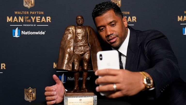 Russell Wilson poses with the Walter Payton trophy (AP Photo/Charlie Riedel)