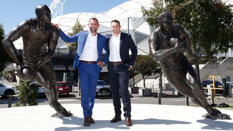 Smith and Billy Slater pose next to their statues outside AAMI Park