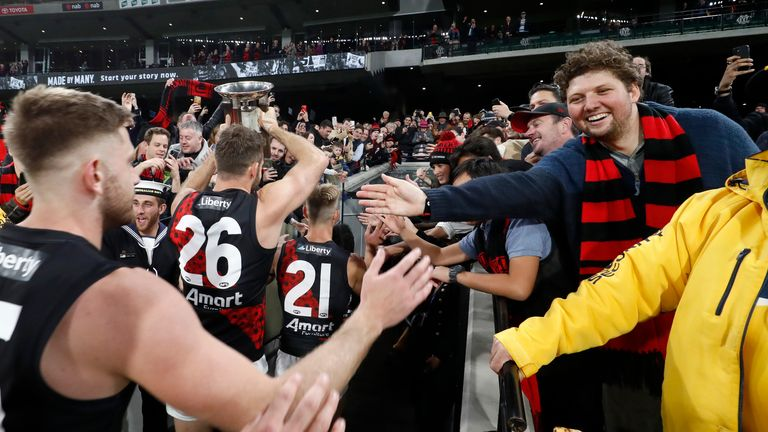 Essendon players celebrate their win with the crowd in Melbourne