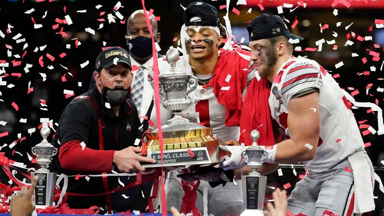 Ohio State head coach Ryan Day, quarterback Justin Fields and linebacker Tuf Borland hold up the trophy after the team's win against Clemson in the Sugar Bowl. (AP Photo/John Bazemore)