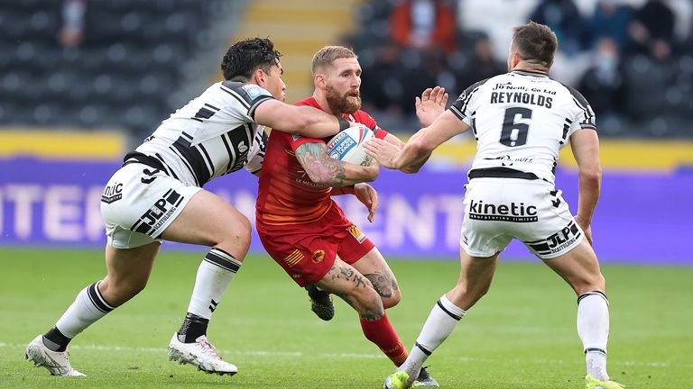 Sam Tomkins in action with Hull FC's Andre Savelio and Josh Reynolds