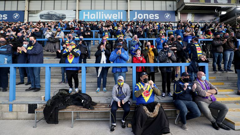 Warrington Wolves fans applaud the players as they come out