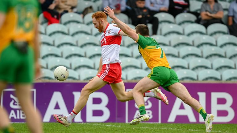 Conor Glass of Derry kicks a point despite the attention of Eoghan Ban Gallagher of Donegal