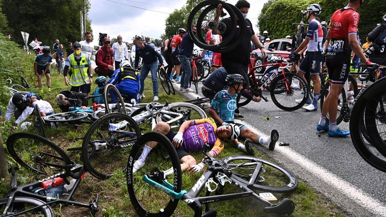 Kristian Sbaragli (left) and Bryan Coquard, (right) lie on the ground after crashing during the first stage of the Tour de France