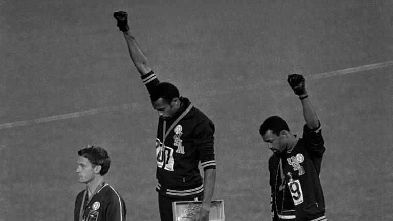 US athletes Tommie Smith (centre) and John Carlos protesting on the podium in Mexico City on October 16 in 1968
