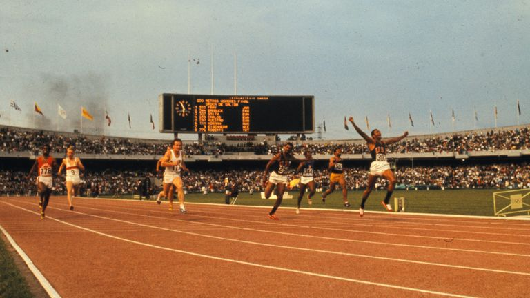 Smith with his arms raised winning gold in the 200m in 1968